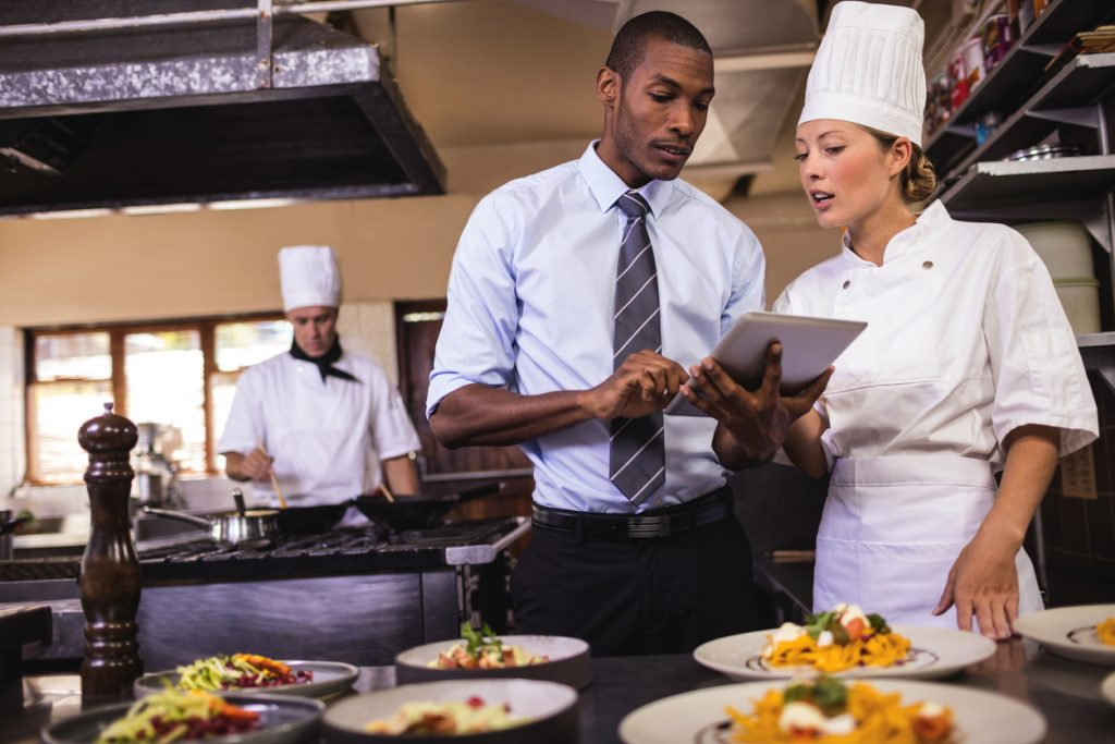 Male manager and female chef using digital tablet in restaurant kitchen